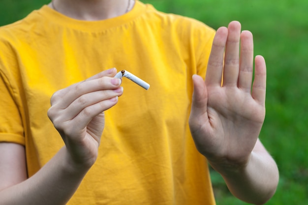 Przestań palić papierosy koncepcja. portret piękny uśmiechnięty dziewczyny mienie łamał papieros w rękach. szczęśliwa kobieta rzuca palenie papierosów. porzuć zły nawyk, pojęcie opieki zdrowotnej. zakaz palenia.