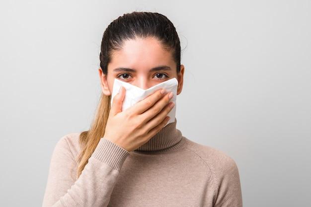 Przestań rozprzestrzeniać koronawirusa. młoda chora kobieta z muchą lub wirusem, kichająca i kaszląca w masce lub serwetce, wyglądająca bardzo beznadziejnie