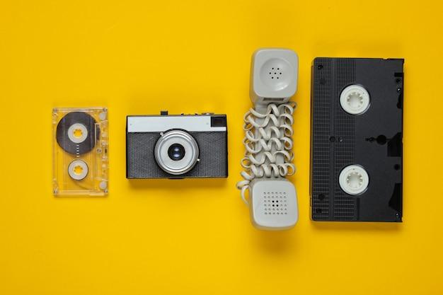 Przestarzała słuchawka, kaseta audio i wideo, retro aparat na żółto