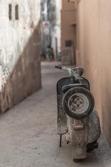 Przestarzały indyjski motocykl zaparkowany w wąskiej uliczce. styl grunge, dekontrastowany.