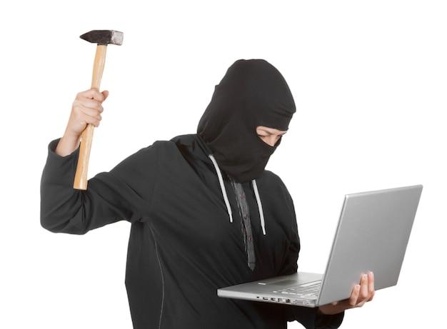Przestępca hakerka nosząca kaptur w czarnych ubraniach i kominiarkę niszczy laptopa młotkiem na białym tle