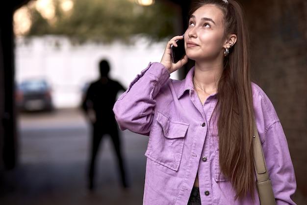 Przestępca stalking kobieta, popełniająca przestępstwo, gdy ofiara spacerowała samotnie, rozmawiała przez telefon