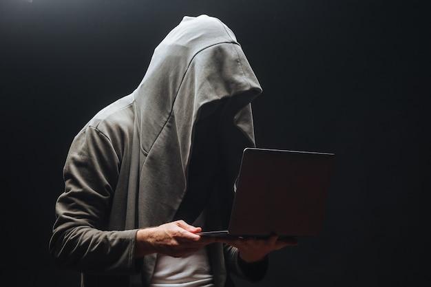 Przestępca z laptopem w kapturze w nocy
