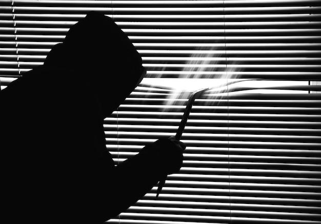 Przestępca z łomem podgląda przez okno. stare żaluzje. czarno-białe zdjęcie.