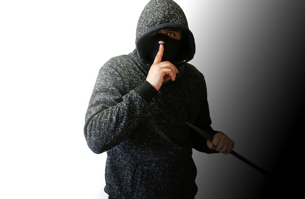 Przestępca z łomem przy drzwiach. rabuś włamujący się do domu.
