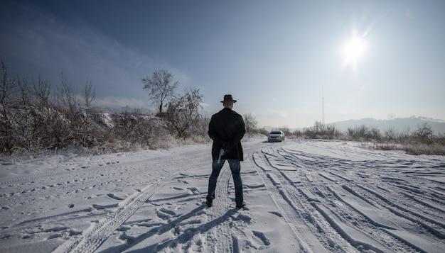 Przestępca z pistoletem na zewnątrz zima
