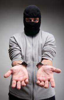 Przestępca zakuty w kajdanki proszący o wolność