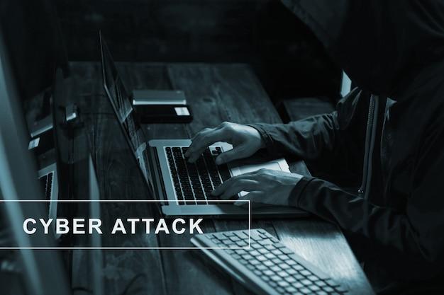 Przestępczość internetowa. hacker za pomocą laptopa i hasła hack code w ciemnym pokoju