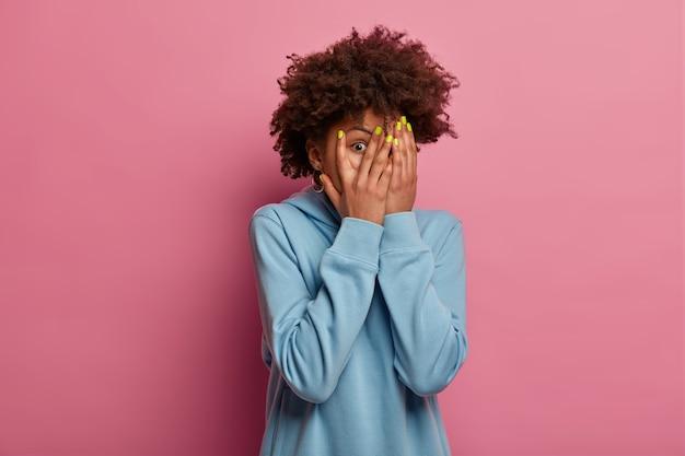 Przestraszona afroamerykanka zakrywa twarz dłońmi, patrzy przez palce, boi się czegoś, nosi niebieską bluzę, chowa się przed czymś przerażającym, odizolowana na różowej ścianie