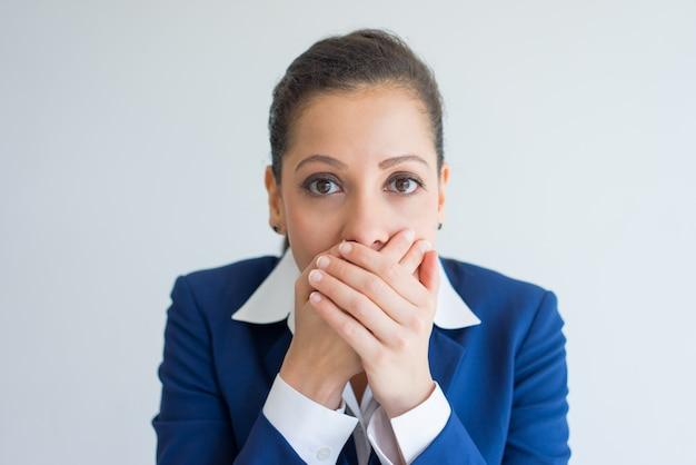Przestraszona biznesowa kobieta utrzymuje ciszę.