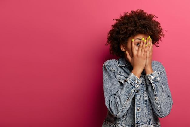 Przestraszona, bojaźliwa kobieta zakrywa twarz dłońmi, patrzy przez palce