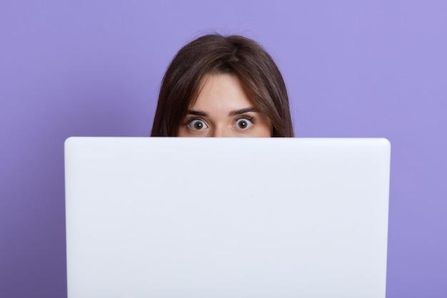 Przestraszona ciemnowłosa kobieta chowająca się za laptopem i patrząc na kamerę oczami pełnymi strachu, boi się czegoś, chce, żeby ktoś jej nie zobaczył, odizolowana na liliowej ścianie.