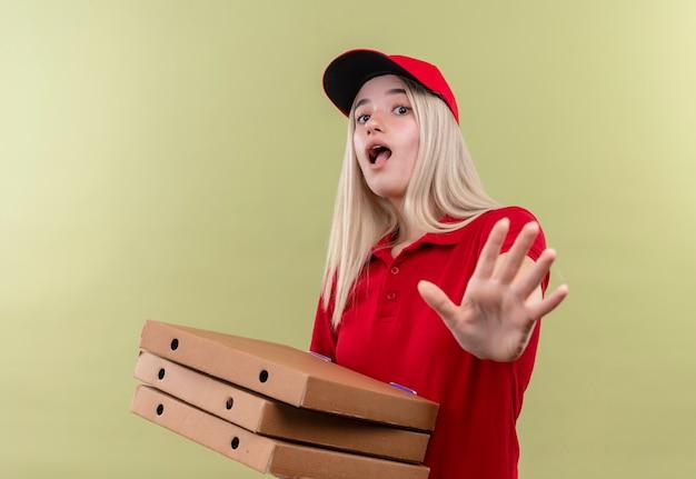 Przestraszona dostawa młoda dziewczyna ubrana w czerwoną koszulkę w czapce trzyma pudełko po pizzy pokazując gest stop na na białym tle zielonym tle