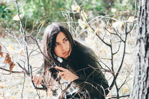 Przestraszona dziewczyna jest sama w lesie, chowa się wśród żółtych liści jesienią.
