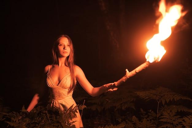 Przestraszona dziewczyna w ciemnym lesie z pochodnią.