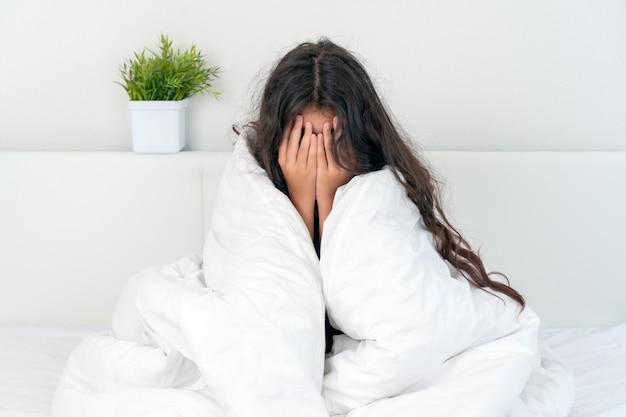 Przestraszona dziewczynka siedzi w łóżku, zasłaniając twarz rękami