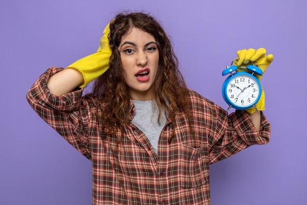 Przestraszona kładąca dłoń na głowie młoda sprzątaczka w rękawiczkach trzymająca budzik