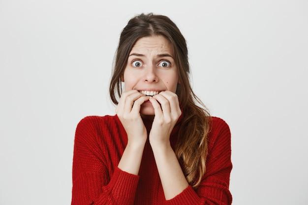 Przestraszona kobieta gryzie paznokcie w panice