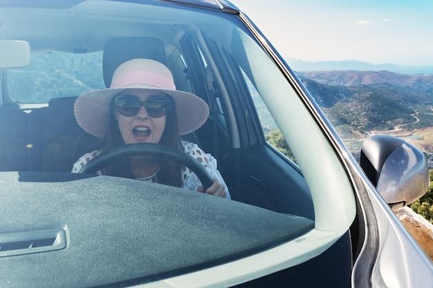 Przestraszona kobieta krzyczy podczas jazdy samochodem