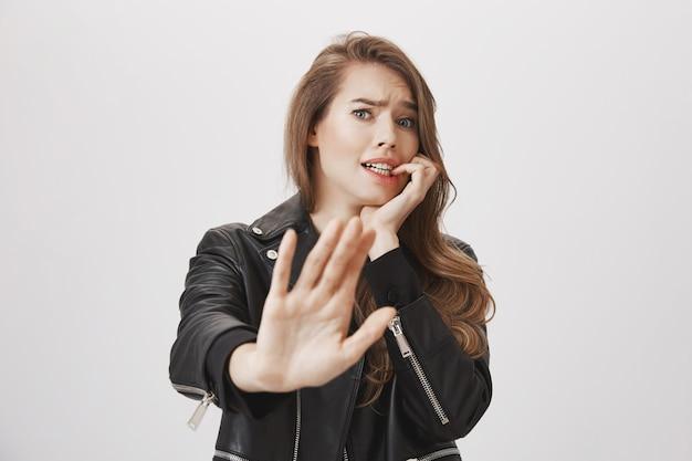 Przestraszona kobieta prosząca o zatrzymanie się, nerwowo wyciągnij rękę do przodu