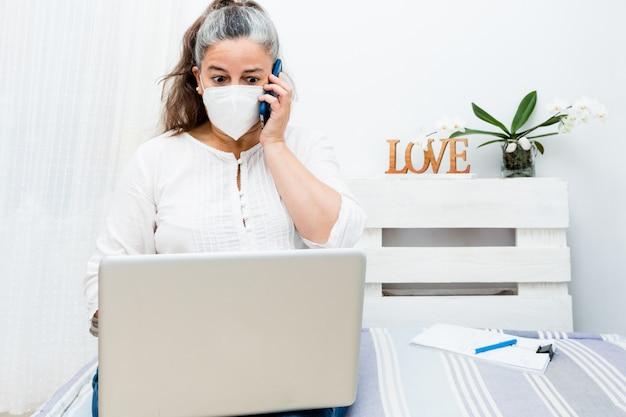 Przestraszona kobieta siedzi na domowej kanapie za pomocą laptopa i dzwoniąc telefonicznie z maską antywirusową