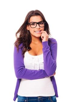 Przestraszona kobieta ubrana w modne okulary i obgryzająca paznokcie
