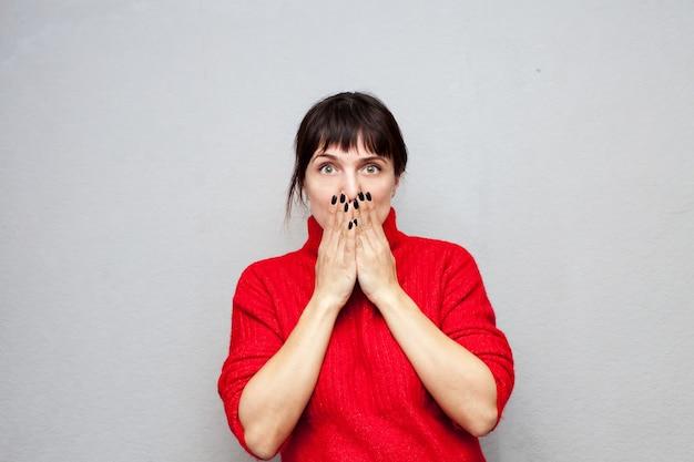 Przestraszona kobieta w czerwonym swetrze zakrywającym usta rękami na szarej ścianie