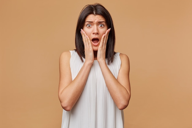 Przestraszona kobieta w panice zdenerwowana przestraszona, ubrana w białą sukienkę, trzymająca dłonie na twarzy, trzyma dłonie w pobliżu policzków, otwiera usta jak lęk, odizolowana