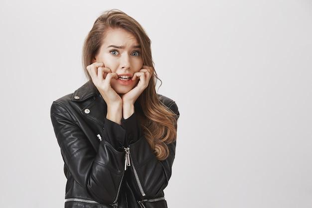 Przestraszona kobieta wyglądająca na zaniepokojoną i zdenerwowaną, gryząc palce