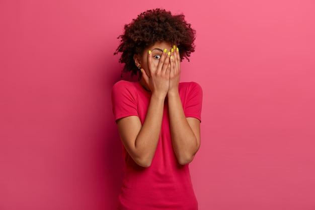Przestraszona kobieta z kręconymi włosami zakrywa twarz dłońmi, boi się czegoś, wyraża strach, patrzy i zerka przez palce, chowa się, nosi luźną koszulkę, pozuje na różowej ścianie