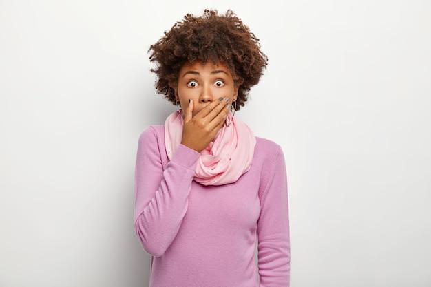 Przestraszona kobieta zdaje sobie sprawę, że plotki o tragedii są prawdziwe, wstrzymuje oddech, trzyma dłoń na ustach, patrzy ze zdziwieniem, nosi fioletowy golf, odizolowany na białym tle.
