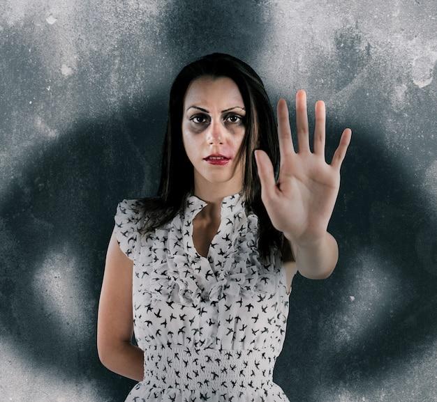 Przestraszona kobieta ze siniakami i zadrapaniami z cieniem mężczyzny za nią