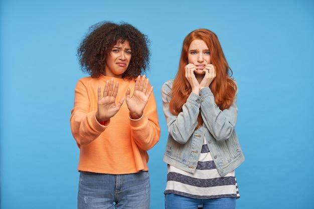 Przestraszona kręcona ciemnoskóra brunetka dama unosząca ręce w geście ochronnym patrząc z przerażoną twarzą, pozująca nad niebieską ścianą z przestraszoną rudą przyjaciółką