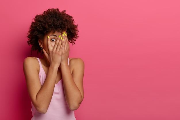 Przestraszona kręcona kobieta zakrywa twarz dłońmi i zagląda przez palce