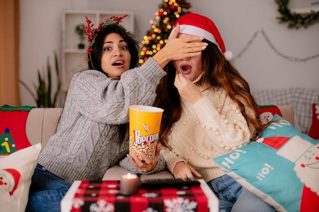 Przestraszona ładna młoda dziewczyna z wieńcem ostrokrzewu zakrywa oczy swojej przyjaciółki jedzącej popcorn, siedząc na fotelu boże narodzenie w domu