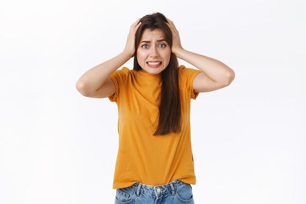 Przestraszona lub zawstydzona młoda atrakcyjna kobieta, chwyta głowę, zaciska zęby w panice i zmartwieniu, widzi coś niebezpiecznego lub kłopotliwego, utknęła w trudnej sytuacji, stoi na białym tle