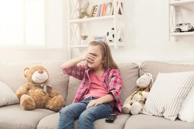 Przestraszona mała dorywczo dziewczyna ogląda telewizję. przerażona dziewczynka siedzi na kanapie z zamkniętymi oczami, sama w domu, oglądając zakazane straszne filmy ze swoimi zabawkowymi przyjaciółmi pluszowymi misiami i owcami, kopia przestrzeń