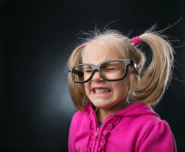 Przestraszona mała dziewczynka w śmiesznych dużych okularach