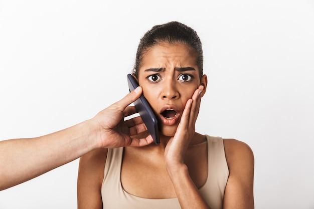 Przestraszona młoda afrykańska kobieta siedzi, podczas gdy ręka mężczyzny trzyma telefon komórkowy przy jej uchu na białym tle