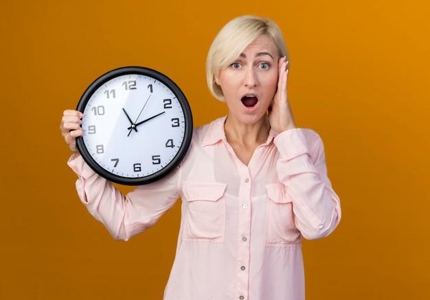 Przestraszona młoda blond słowiańska kobieta trzyma zegar ścienny i kładzie rękę na świątyni na białym tle na pomarańczowej ścianie