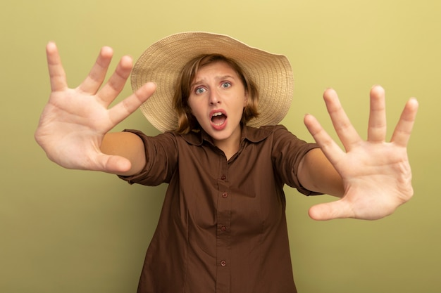 Przestraszona młoda blondynka w kapeluszu plażowym, wykonująca gest zatrzymania na oliwkowozielonej ścianie