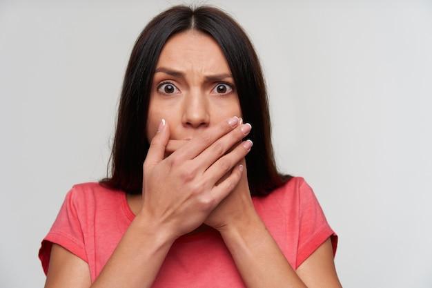 Przestraszona młoda brązowooka ciemnowłosa kobieta z przypadkową fryzurą, wyglądająca na przestraszoną i marszczącą brwi, stojąca z rękami na ustach