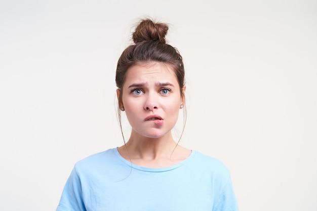 Przestraszona młoda brązowowłosa dama z przypadkową fryzurą gryząca niepokojąco dolną wargę, patrząc podekscytowana z przodu, odizolowana na białej ścianie z opuszczonymi rękami