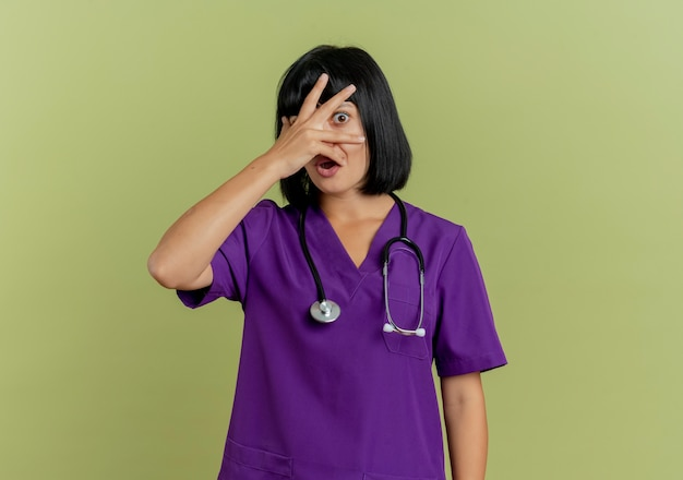 Przestraszona młoda brunetka lekarka w mundurze ze stetoskopem kładzie dłoń na twarzy i patrzy przez palce odizolowane na oliwkowym tle z miejsca na kopię