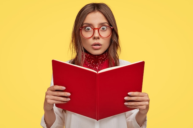 Przestraszona młoda brunetka w okularach pozuje na żółtej ścianie