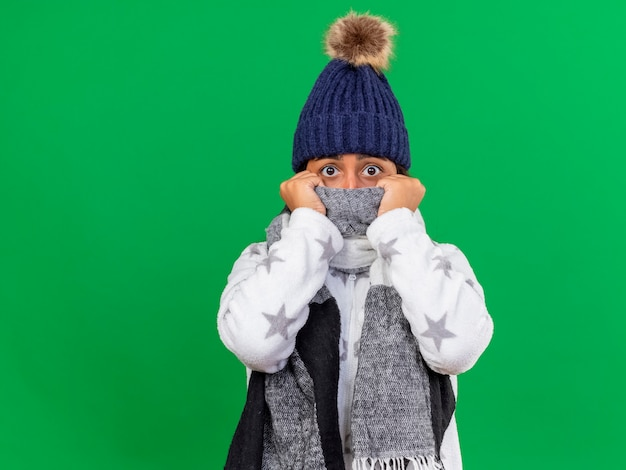 Przestraszona młoda chora dziewczyna na sobie czapkę zimową z szalikiem i zakrytą twarz z szalikiem na białym tle na zielonym tle