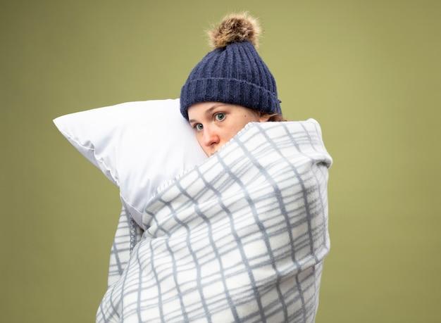 Przestraszona młoda chora dziewczyna patrząc z boku w białym szlafroku i zimowej czapce z szalikiem zawiniętym w kraciastą poduszkę