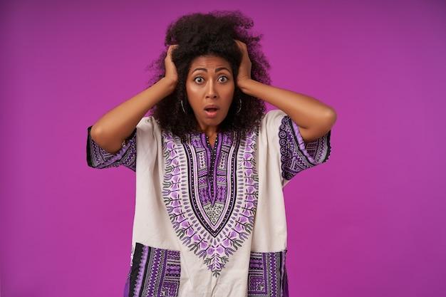 Przestraszona młoda ciemnoskóra kobieta z kręconymi włosami, ubrana w białą wzorzystą koszulę, trzymająca głowę z podniesionymi rękami oraz z szeroko otwartymi oczami i ustami, odizolowana na fioletowo