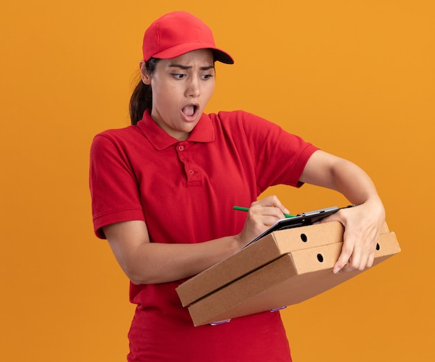 Przestraszona młoda dziewczyna dostawy ubrana w mundur i czapkę pisze coś w schowku na pudełkach po pizzy na białym tle na pomarańczowej ścianie