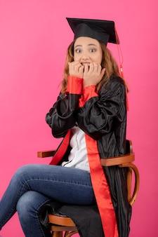 Przestraszona młoda dziewczyna nosi suknię ukończenia szkoły i obgryza paznokcie.